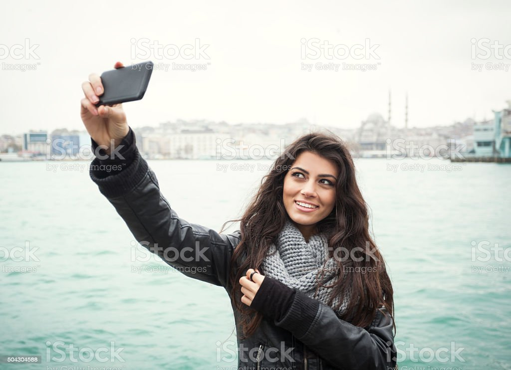 Young Turkish Woman Taking A Selfie At The Seaside stock photo