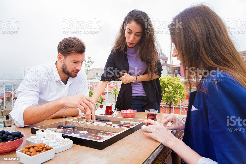 Young Turkish woman teaches friends how to play tavla stock photo