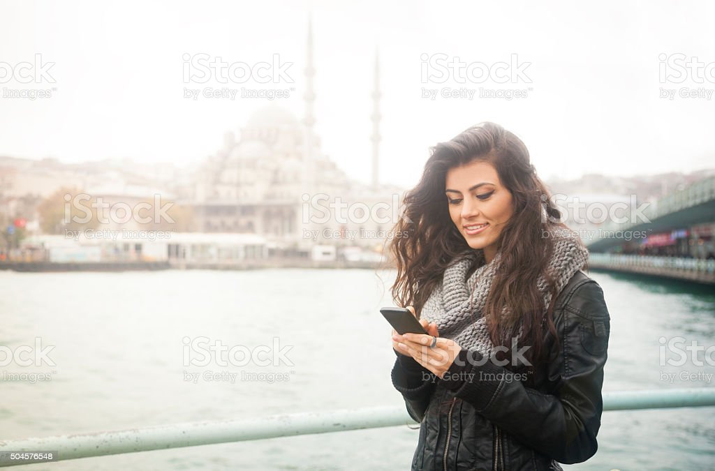 Young Turkish Woman Texting On Phone In Istanbul Near Water stock photo