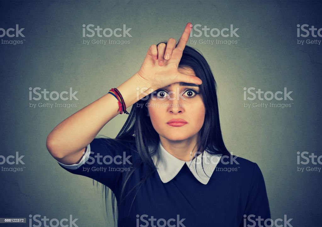 young unhappy woman giving loser sign on forehead stock photo
