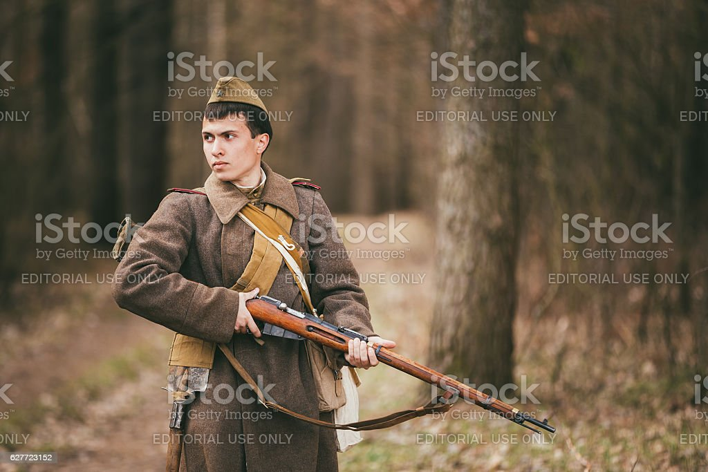 Young unidentified re-enactor dressed as Soviet soldier gunner goes stock photo