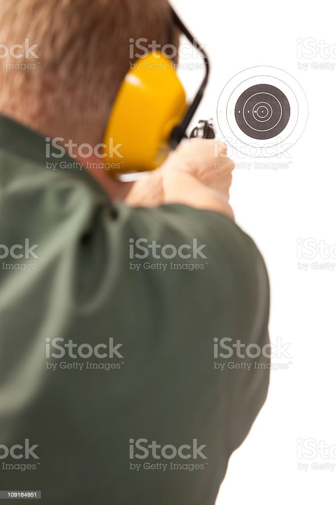 Young uniformed man practicing shooting in the shooting-range stock photo