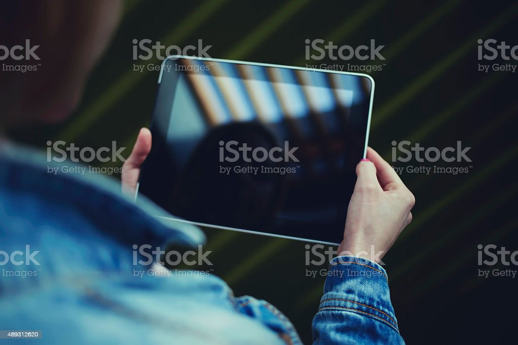 Young university student girl browsing internet via touch pad stock photo
