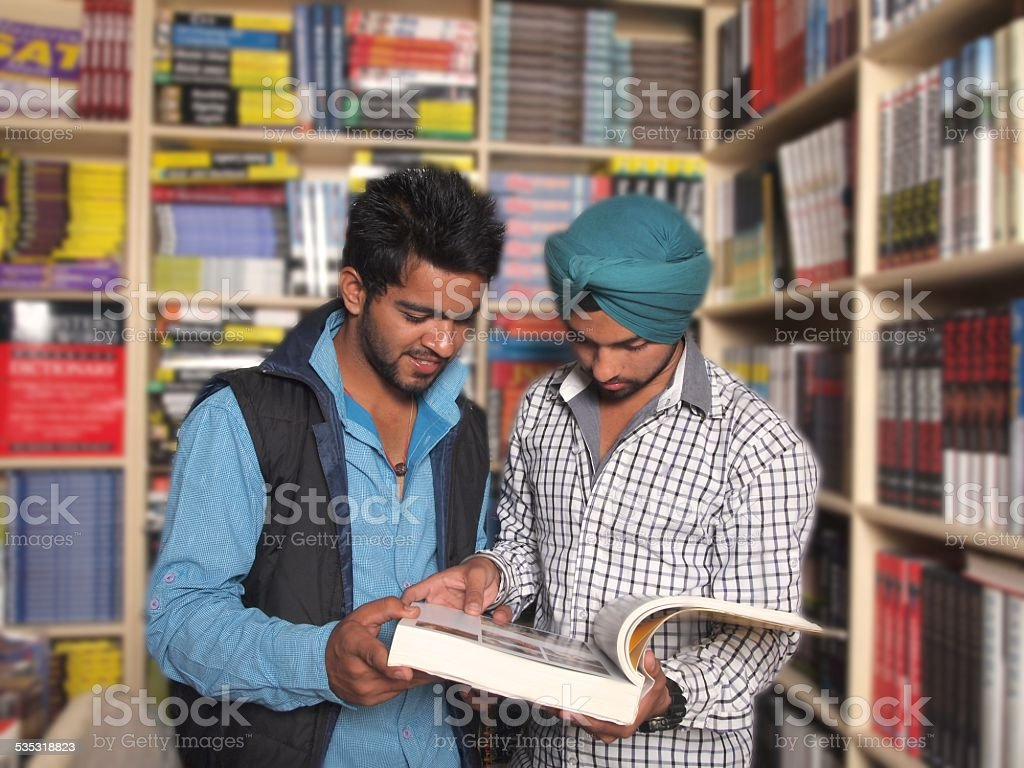 Young university students reading book in library. stock photo