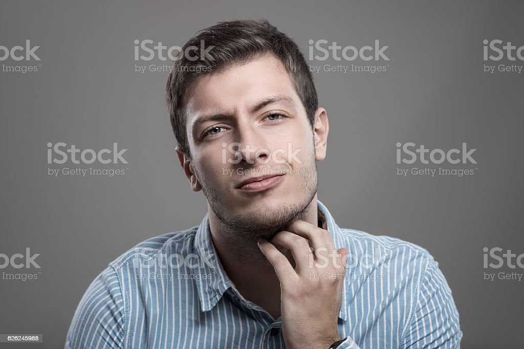 Young unshaven man scratching itchy beard with painful expression stock photo