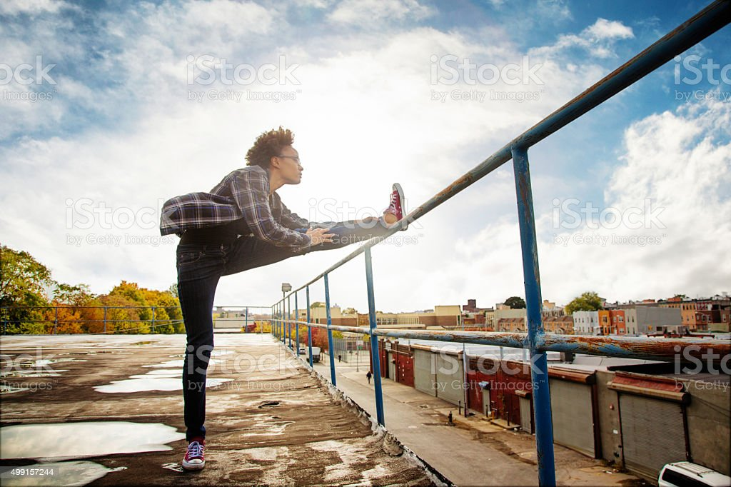 Young urban American black female stretching on Brooklyn rooftop stock photo