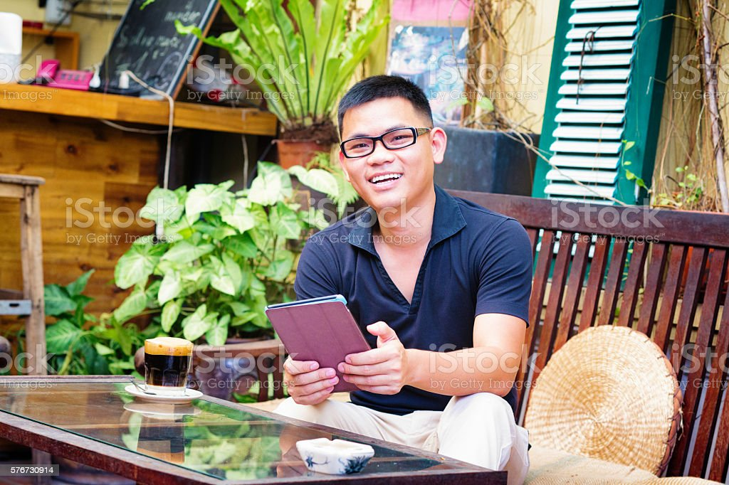 Young Vietnamese male entrepreneur portrait at cafe with tablet stock photo