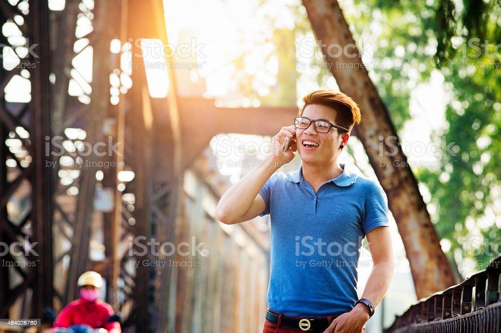 Young Vietnamese man crossing Long Bien Bridge laughing on phone stock photo