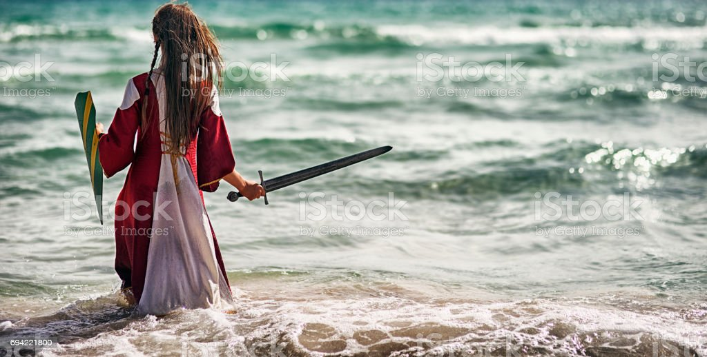 Young viking shieldmaiden practicing with sword stock photo