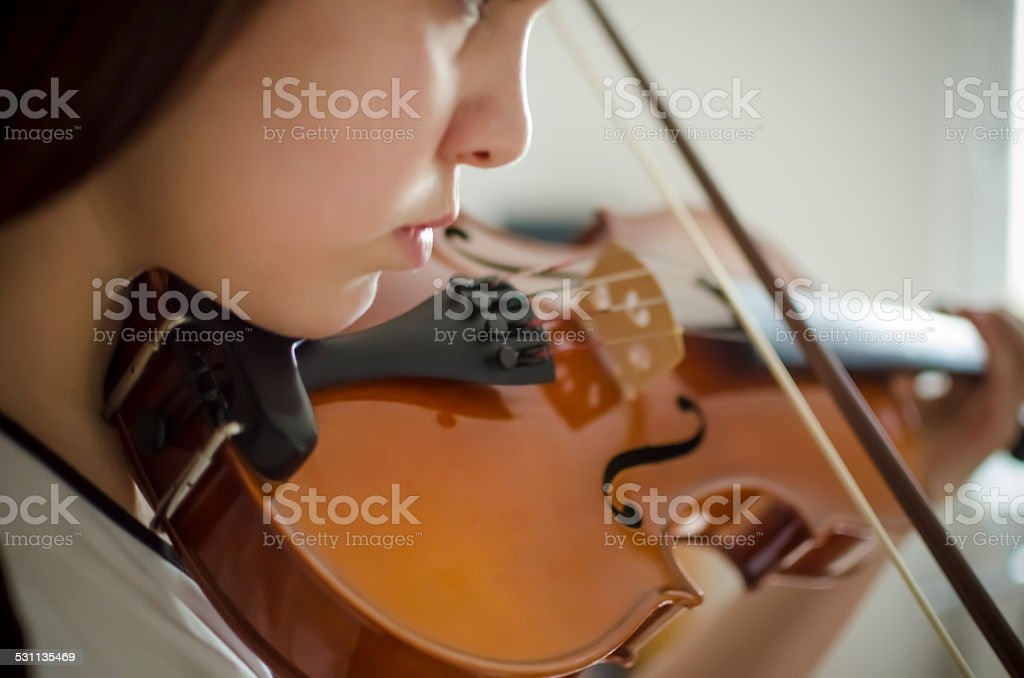 Young violinist playing violin stock photo