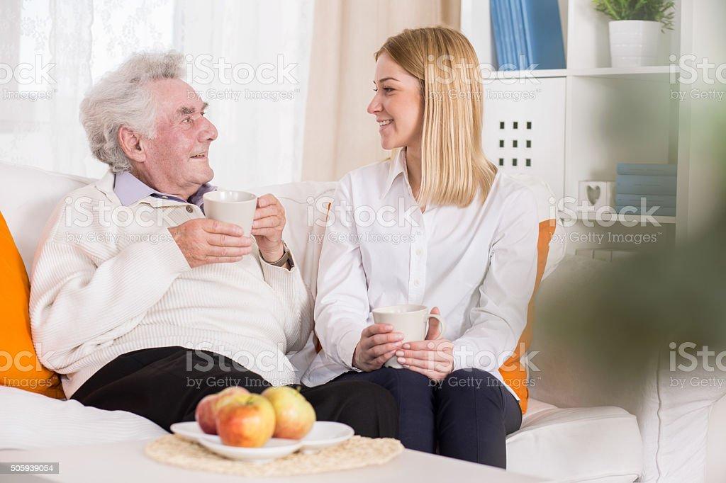 Young volunteer in nursing home stock photo