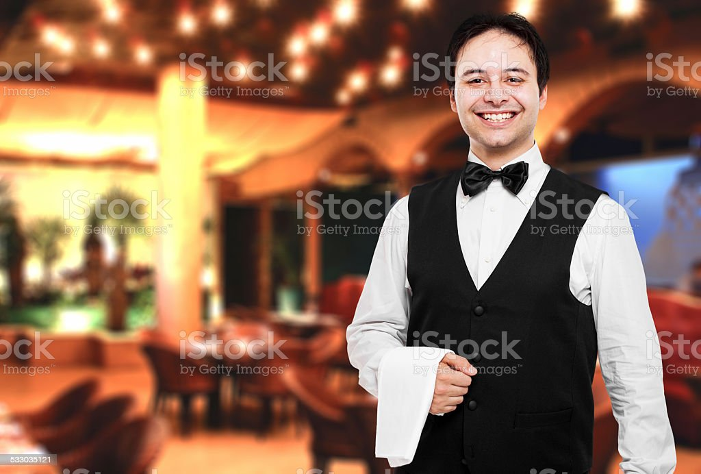 Young waiter at the restaurant stock photo