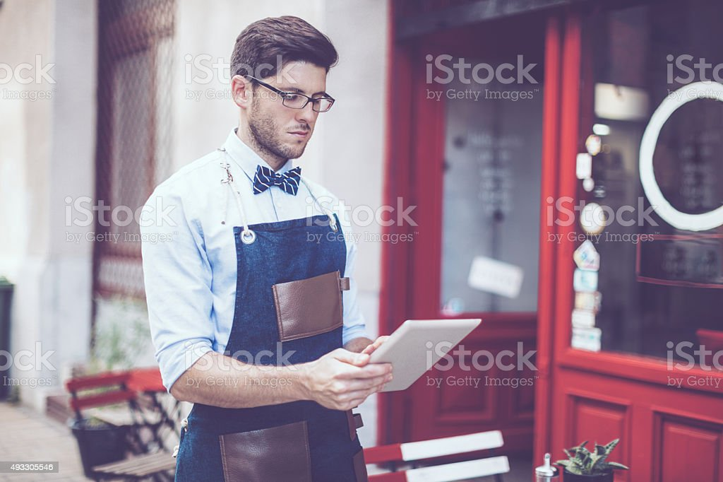 Young waiter is using a digital tablet stock photo