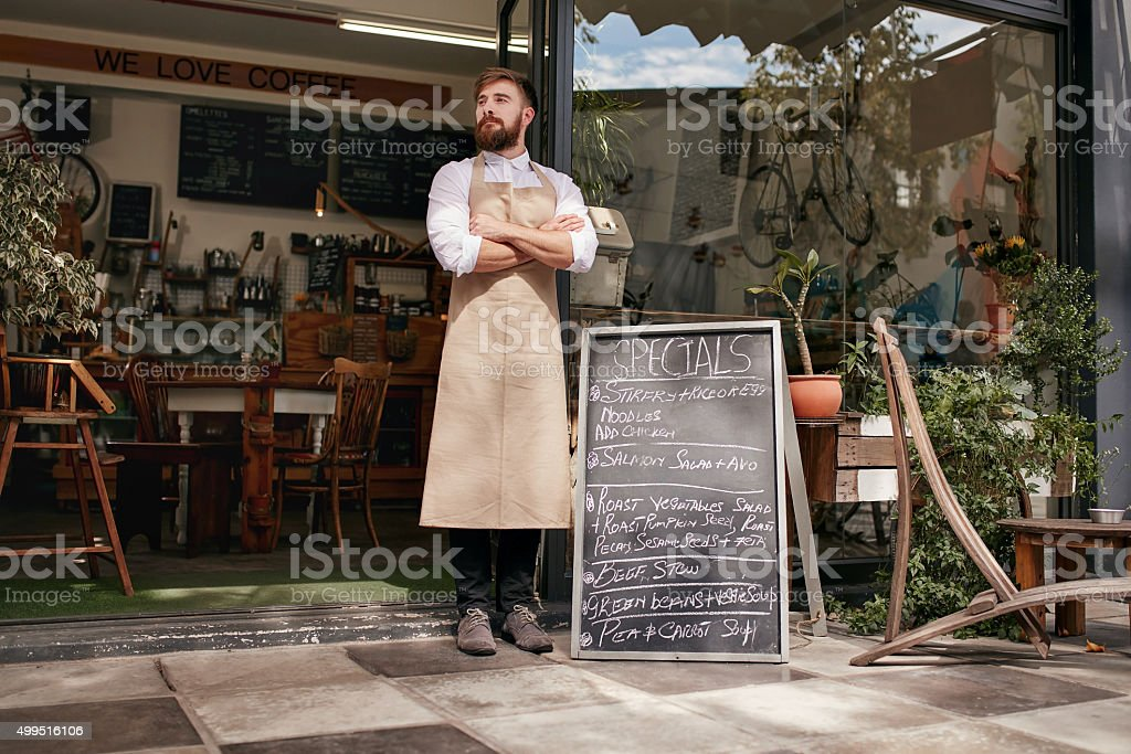Young waiter standing in door of a cafe stock photo