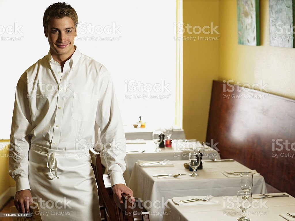 Young waiter standing in restaurant, smiling, portrait royalty-free stock photo