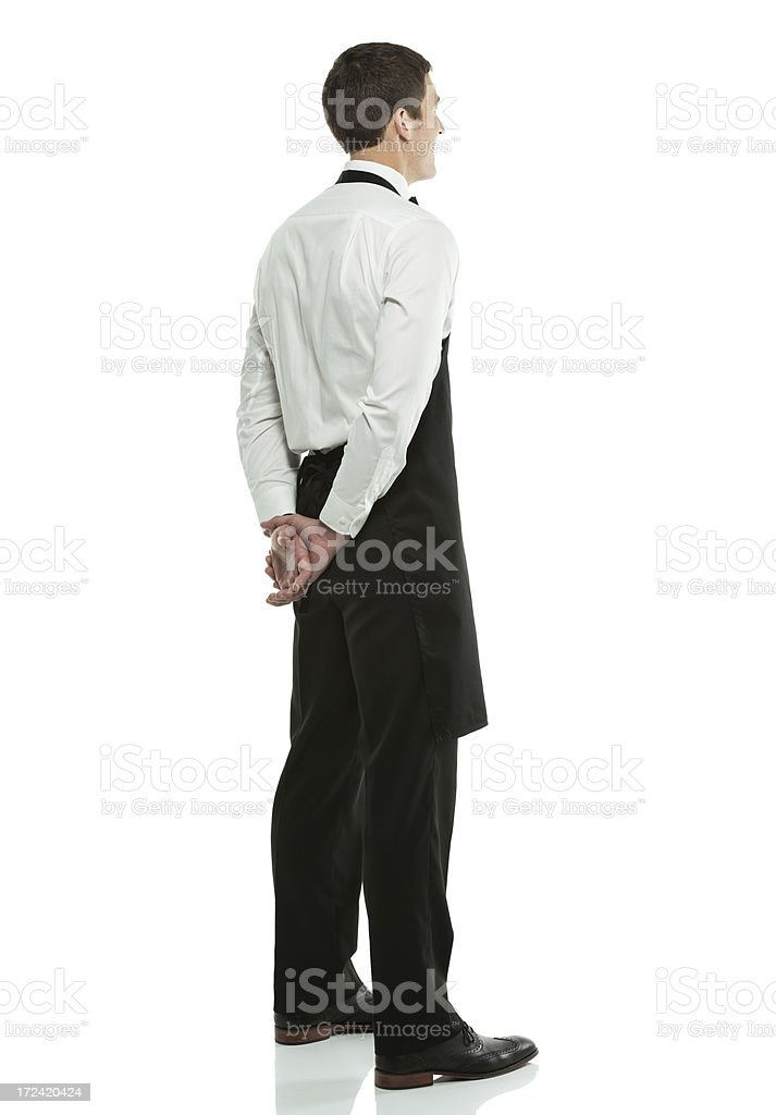 Young waiter standing with his hands behind back royalty-free stock photo