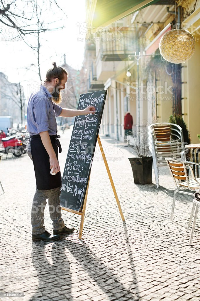 Young waiter updating todays special menu board stock photo