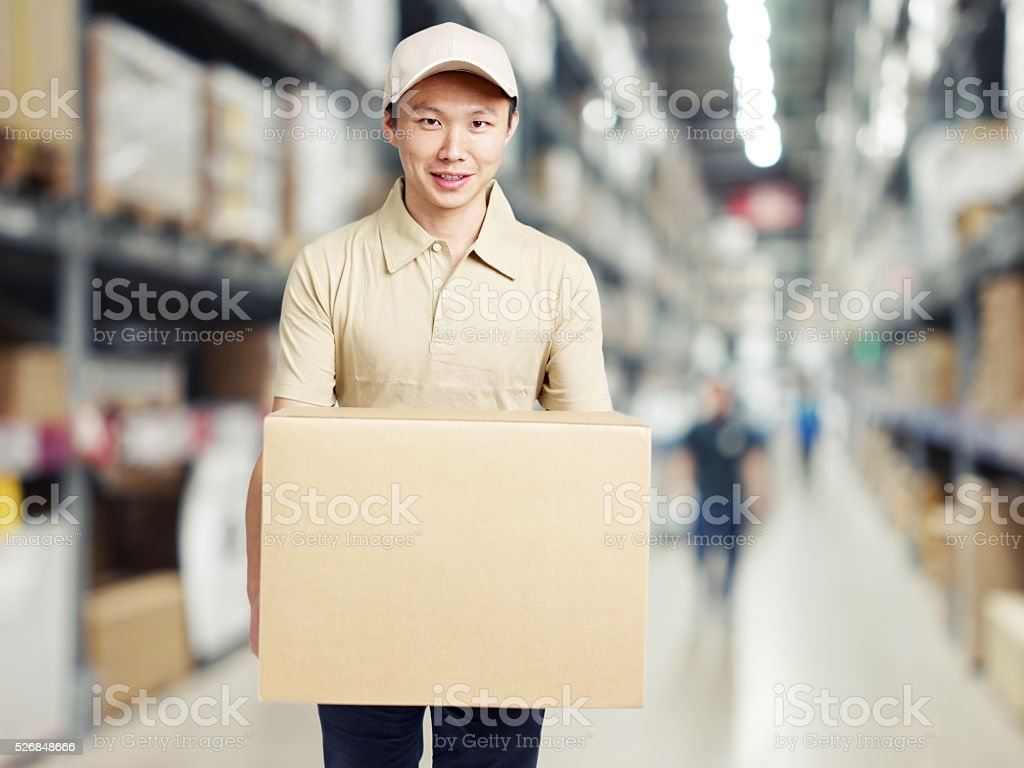 young warehouse worker carrying a cardboard box stock photo