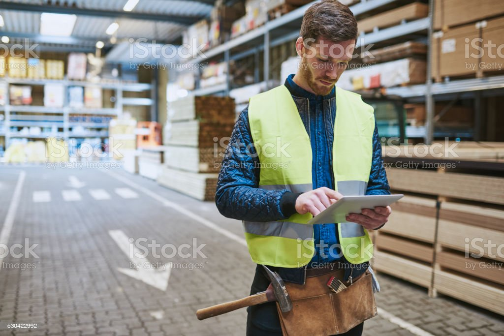 Young warehouse worker consulting a tablet stock photo