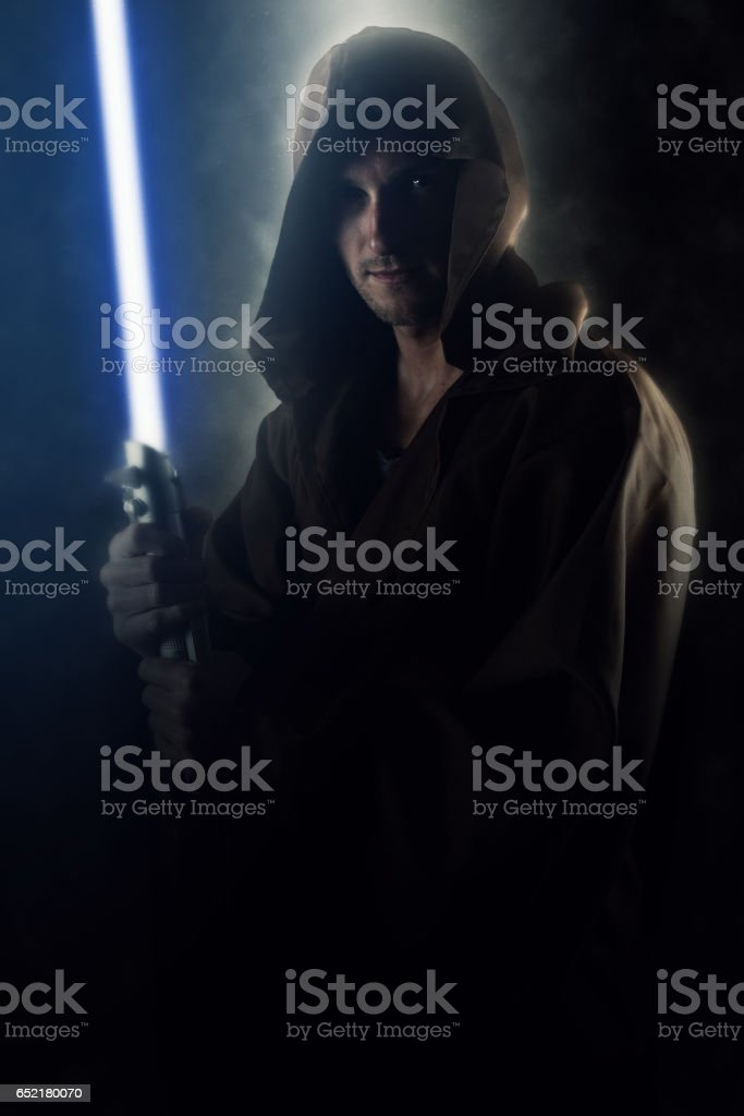 Young warrior holding a lightsaber stock photo