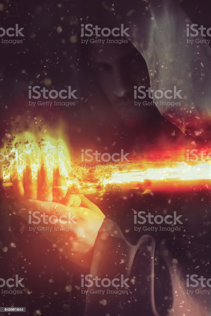 Young warrior holding a saber in fire stock photo