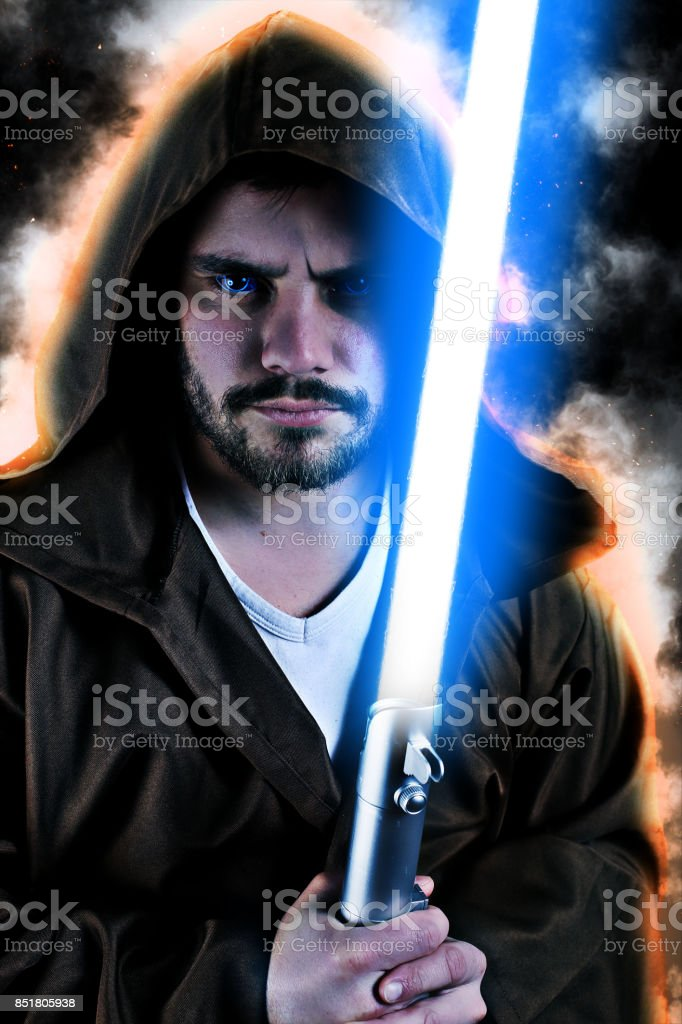 young warrior with brown hooded cape holding a laser sword stock photo