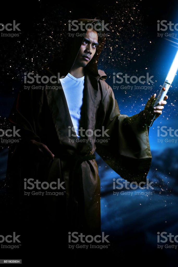 young warrior with brown hooded cape holding a light saber stock photo