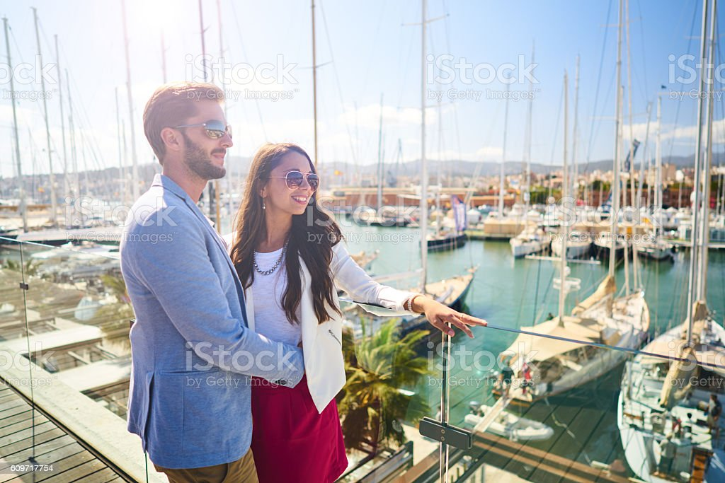 young wealthy couple standing on marina stock photo