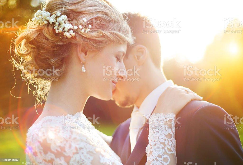 Young wedding couple on summer meadow stock photo