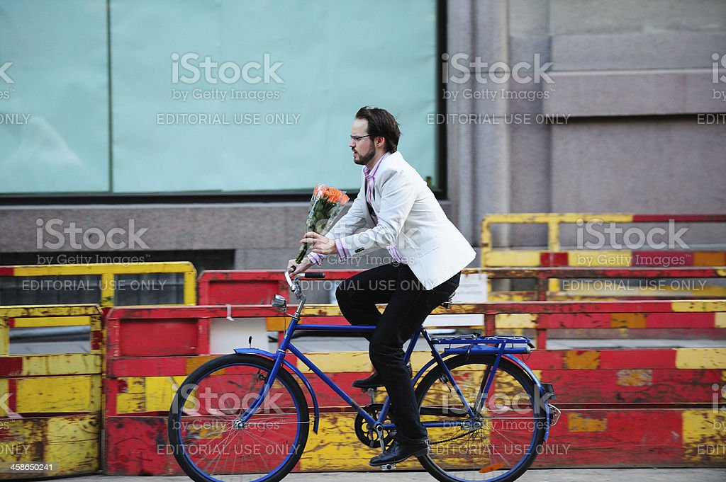 Young well dressed adult male on bike in traffic royalty-free stock photo
