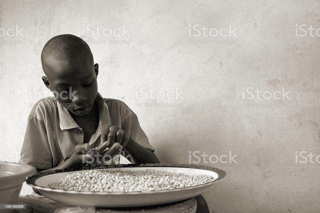 Young West African Boy Sorting Beans royalty-free stock photo