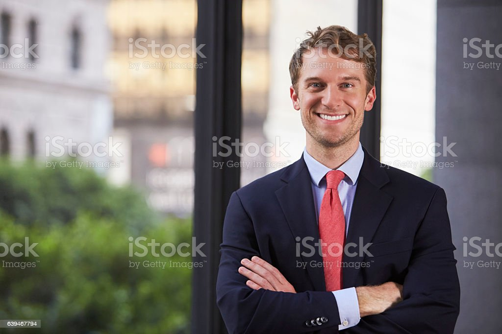 Young white businessman with arms crossed smiling, waist up stock photo