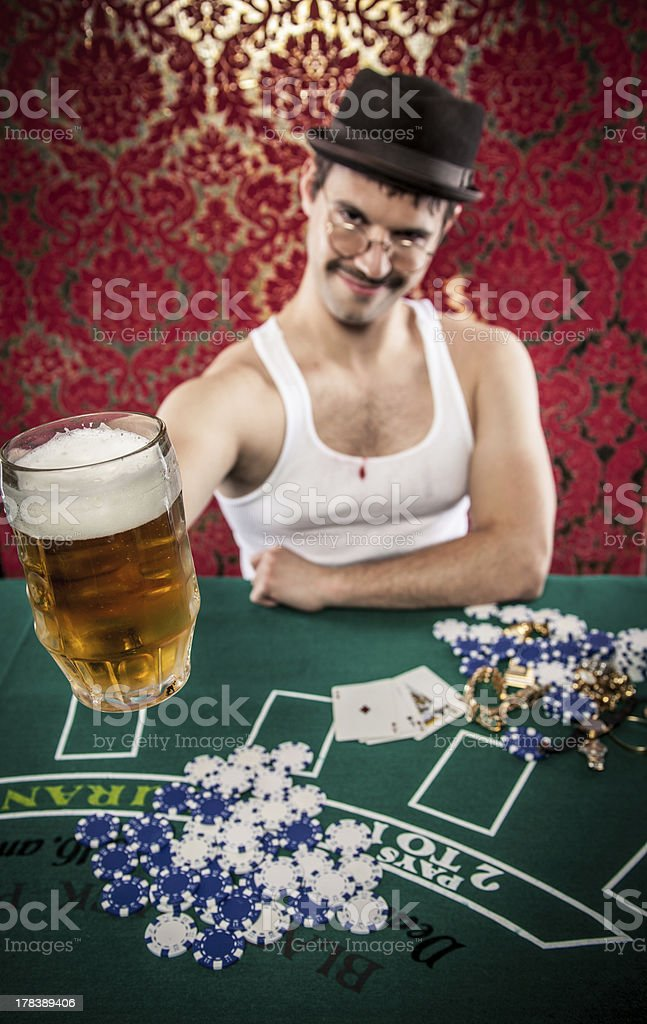 Young white eccentric man in vintage casino toasting beer stock photo