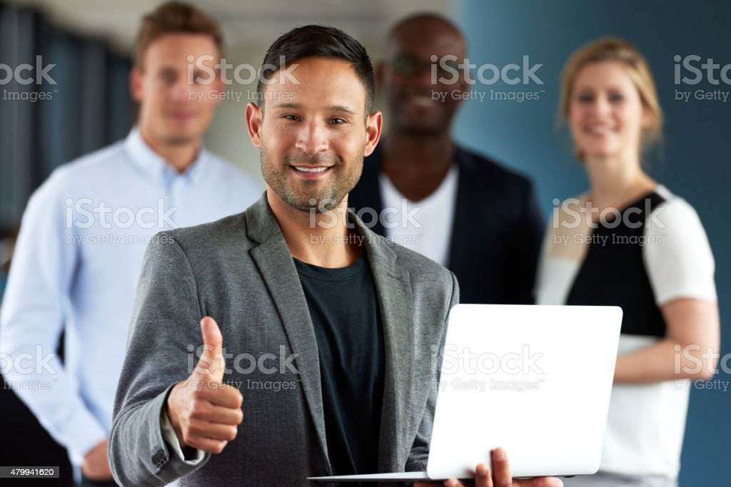 Young white executive making thumbs up sign holding laptop stock photo