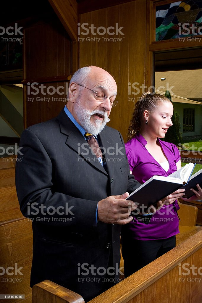 Young White Woman Caucasian Man Standing, Singing, Holding Hymnal Church royalty-free stock photo