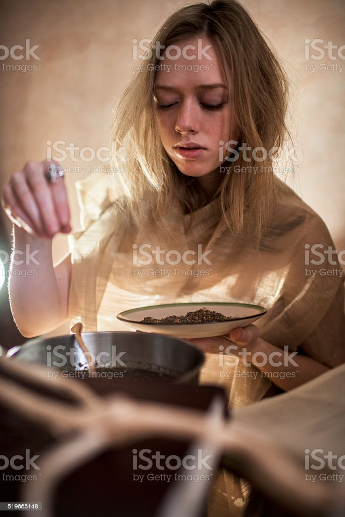 Young witch making a spell. stock photo
