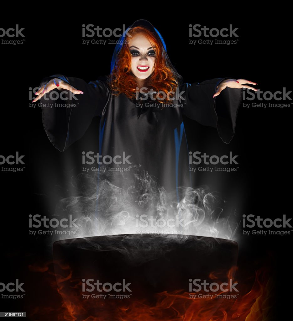 Young witch with cauldron stock photo