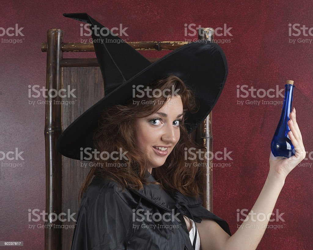 Young witch with potions royalty-free stock photo