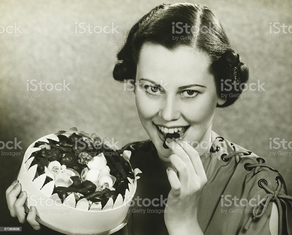 Young woman a chocolate from box, posing, (B&W), portrait stock photo
