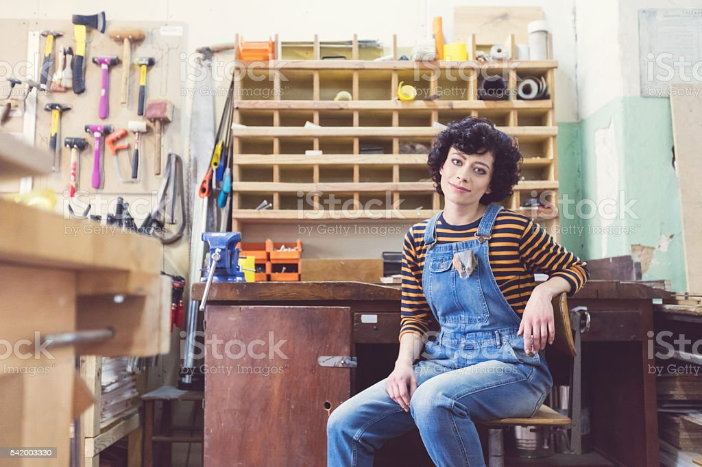 Young woman a construction workshop, learning carpentry stock photo