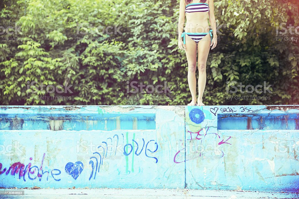 Young woman about to jump into dirty empty swimming pool royalty-free stock photo