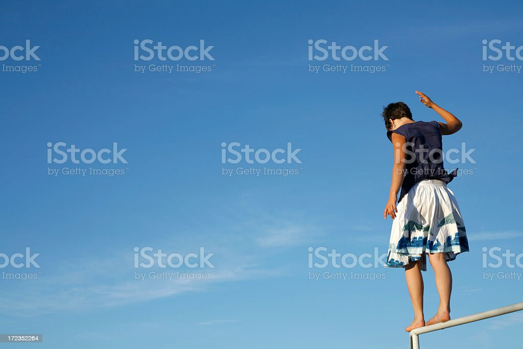 A young woman about to jump off a rail royalty-free stock photo