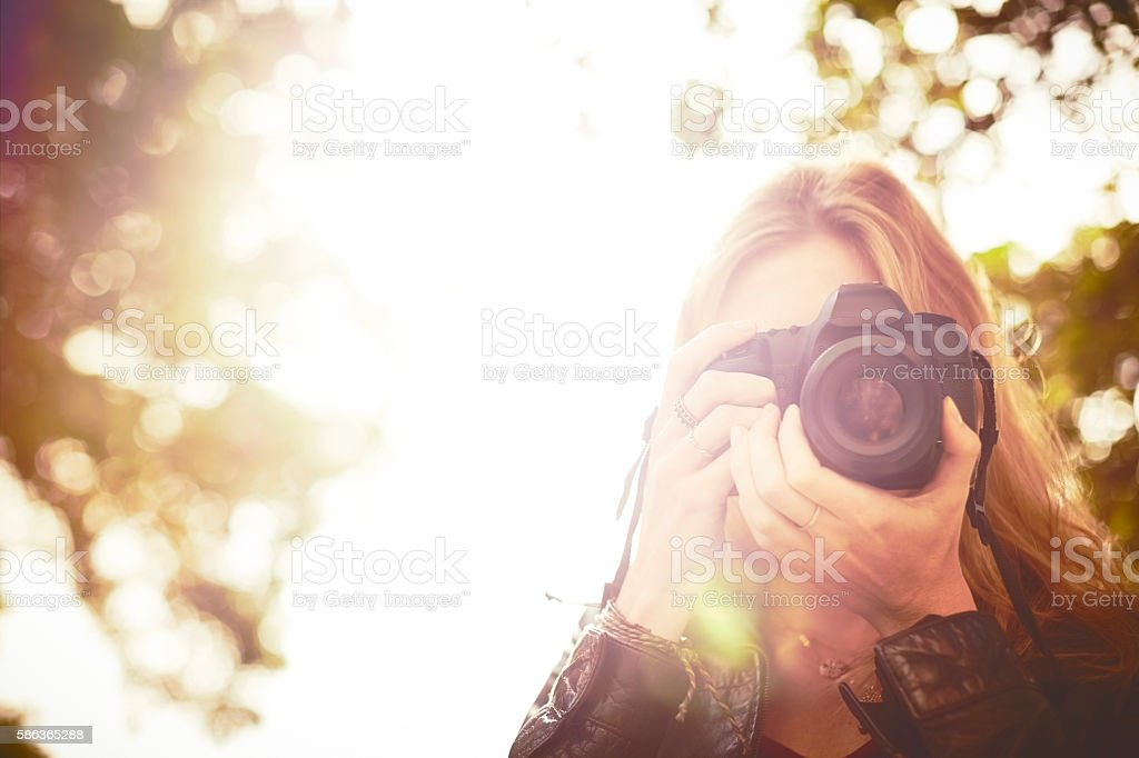 Young woman adjusting camera lens while taking picture outdoors stock photo