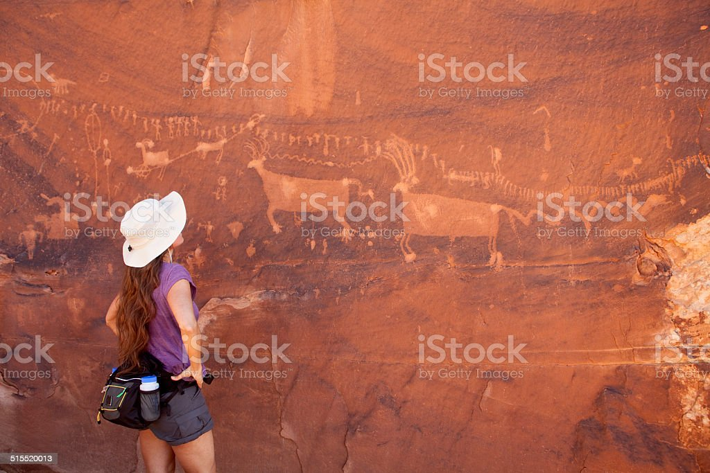 Young woman admires Utah rock art stock photo