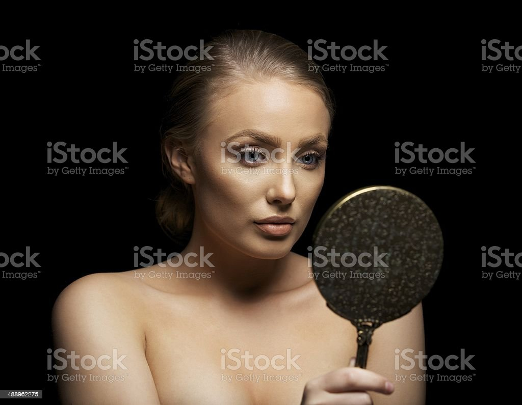 Young woman admiring her beautiful skin in a mirror stock photo