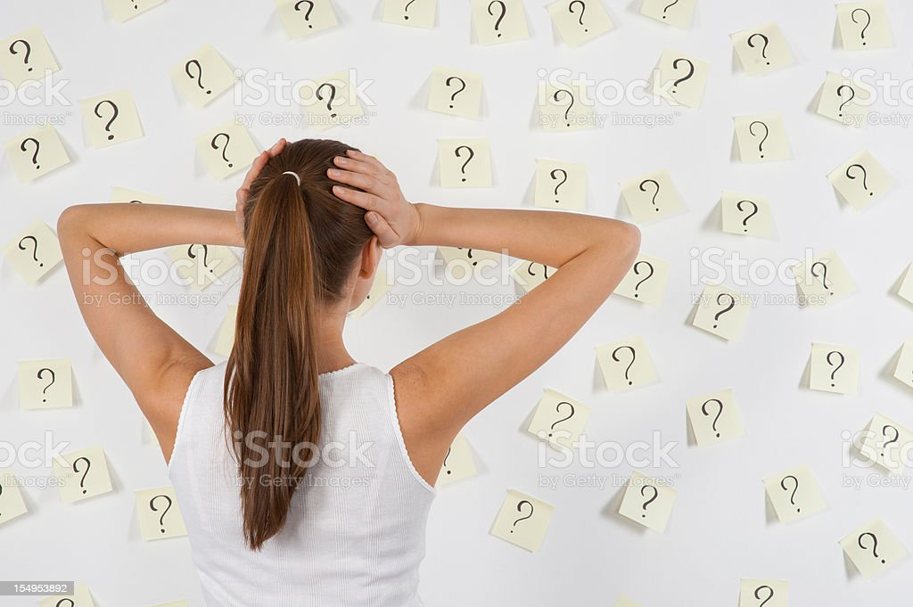 Young woman against stickers with questions stock photo
