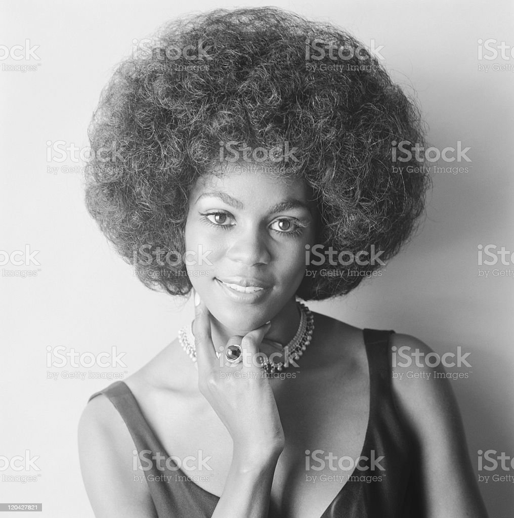 Young woman against white background, smiling, portrait stock photo