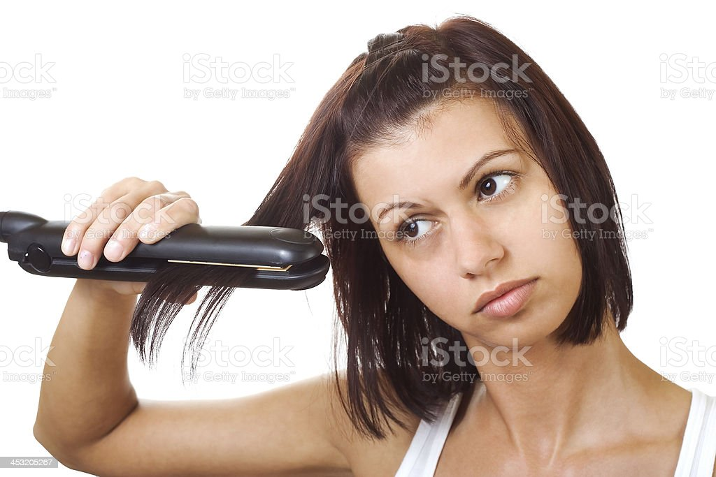 Young woman and a hair straightener stock photo