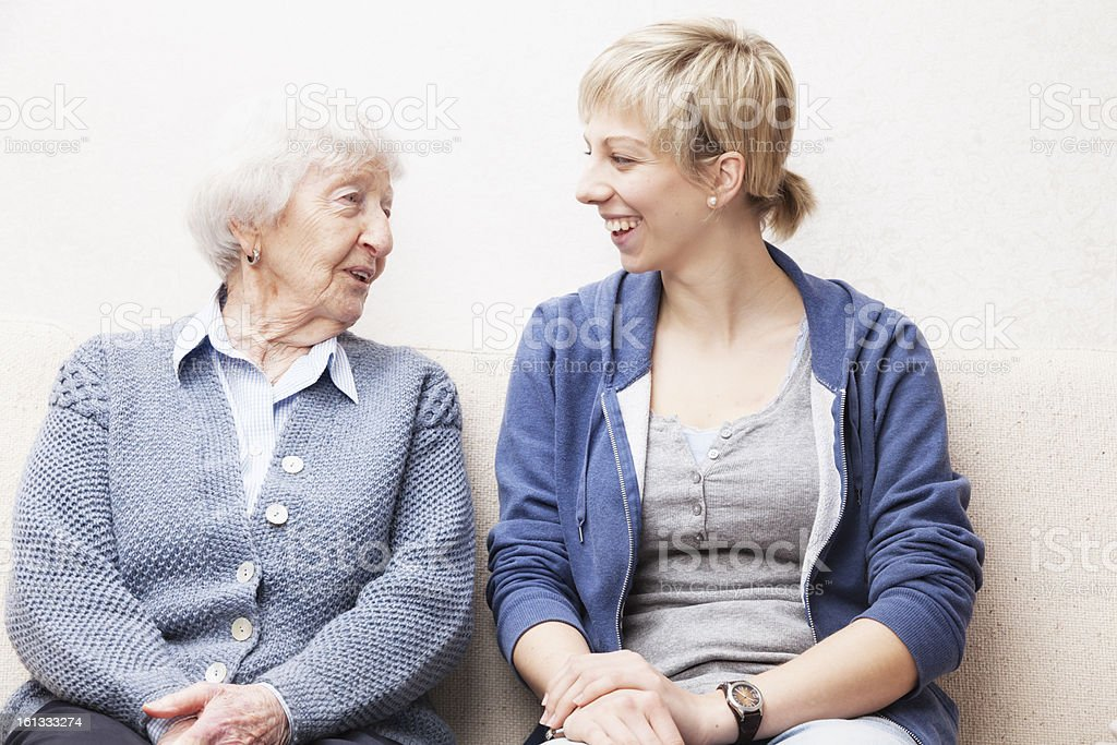 Young woman and a senior woman smiling and talking stock photo