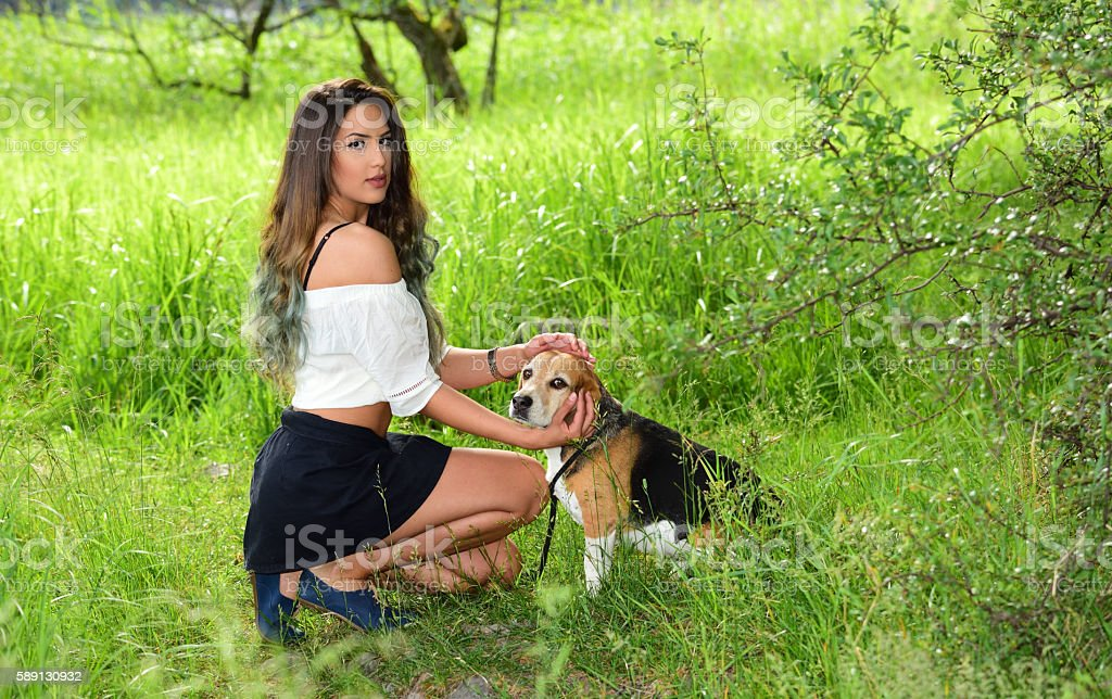 Young woman and beagle dog in the woods stock photo